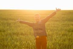 Kind in der Wiese im hohen Gras bei Sonnenuntergang Stockfotos