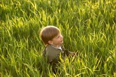 Kind in der Wiese im hohen Gras bei Sonnenuntergang Lizenzfreies Stockbild