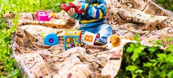 Kind des kleinen Jungen, das auf dem Gras sitzt Lizenzfreies Stockbild