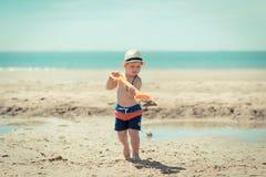 Kind des kleinen Jungen, das auf den Strand geht Stockfotografie
