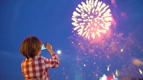 Kind des kleinen Jungen, das Bilder von schönen Feuerwerken in der Anzeige des nächtlichen Himmels des Handys filmt Hände des Bab stock video