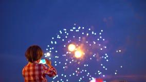 Kind des kleinen Jungen, das Bilder von schönen Feuerwerken in der Anzeige des nächtlichen Himmels des Handys filmt Hände des Bab stock video footage