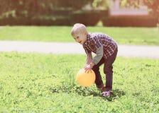Kind des kleinen Jungen, das draußen mit Ball auf dem Gras spielt Stockfoto