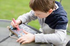 Kind des kleinen Jungen, das eine Liebeserklärung zeichnet Stockfoto