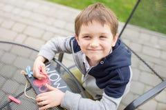 Kind des kleinen Jungen, das eine Liebeserklärung zeichnet Stockfotos