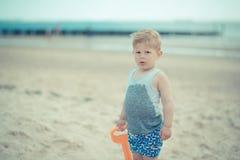 Kind des kleinen Jungen, das mit einem nassen Hemd auf dem Strand steht Lizenzfreies Stockbild