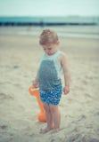 Kind des kleinen Jungen, das mit einem nassen Hemd auf dem Strand steht Stockfoto