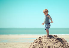 Kind des kleinen Jungen, das vor einer Klippe steht Stockfoto