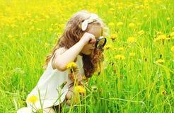 Kind des kleinen Mädchens, das durch eine Lupe schaut Lizenzfreies Stockfoto