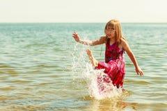 Kind des kleinen Mädchens, das im Seeozeanwasser spritzt Spaß Stockfotografie