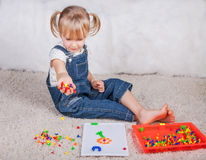 Kind des kleinen Mädchens, das mit Bildungsmosaikstiften spielt Stockbild