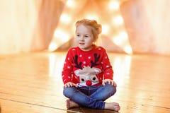 Kind des kleinen Mädchens mit den braunen Augen, die an in der roten Strickjacke sitzen Stockfoto
