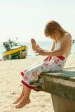 Kind des kleinen Mädchens, das Eiscreme auf Strand isst Sommer Stockbild