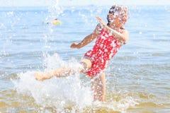 Kind des kleinen Mädchens, das im Seeozeanwasser spritzt Spaß Lizenzfreies Stockfoto