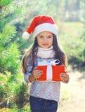 Kind des Weihnachtskleinen Mädchens in Sankt-Hut mit Geschenkbox Lizenzfreie Stockfotos