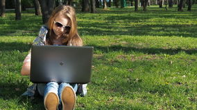 Kind die aan laptop in aard werken Een tiener die zonnebril dragen zit op het gras in het park Meisjes zonnige openluchtdag met L stock videobeelden