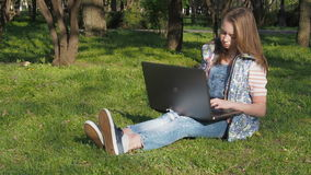 Kind die aan laptop in aard werken Een tiener die zonnebril dragen zit op het gras in het park Meisjes zonnige openluchtdag met L stock video