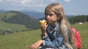Kind die Appelen in Bergen, Hongerig Jong geitje bij Picknick, Meisje bij het Kamperen eten royalty-vrije stock fotografie