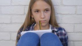 Kind die, Bestuderend, Nadenkend Jong geitje, Peinzende Student Learning Schoolgirl schrijven stock fotografie