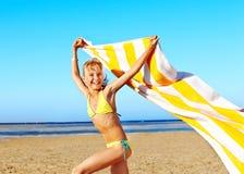 Kind die bij strand met handdoek lopen. royalty-vrije stock afbeelding