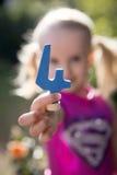 Kind die blauw nummer vier houden Royalty-vrije Stock Foto