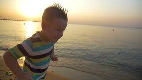 Kind die boos gezicht op het strand maken bij zonsondergang stock videobeelden