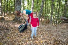 Kind die in bos in de herfst dichtbij moeder met rugzak kijken royalty-vrije stock fotografie