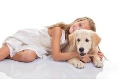 Kind die de hond van het huisdierenpuppy koesteren Stock Foto's