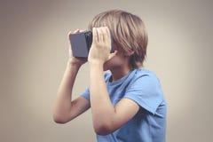 Kind die de Virtuele glazen van het Werkelijkheidsvr karton gebruiken stock foto's