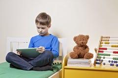 Kind die digitale tabletcomputer thuis met behulp van stock afbeeldingen