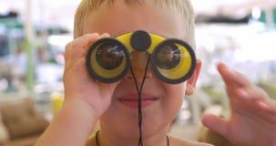 Kind die door de verrekijkers kijken stock videobeelden