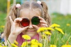 Kind die door gekleurd glas (Fotofilters) kijken op dandeli Royalty-vrije Stock Foto