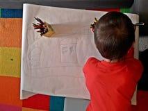 Kind die een bolwerk trekken op een groot blad van document stock foto