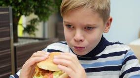 Kind die een broodje met kip, kaas en greens in een snel voedselrestaurant eten stock footage