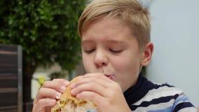 Kind die een broodje met kip, kaas en greens in een snel voedselrestaurant eten stock videobeelden