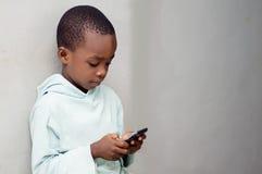 Kind die een celtelefoon behandelen stock fotografie