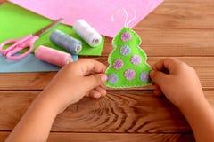 Kind die een gevoelde Kerstboom in zijn handen houden Groene die stoffenkerstboom met roze en blauwe ballen wordt verfraaid Stock Afbeeldingen