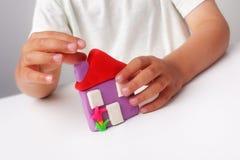 Kind die een huis van de spelklei buiding Stock Afbeelding