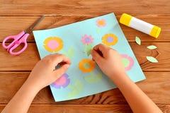 Kind die een kaart met bloemen doen Het kind houdt een document blad in zijn handen en plakt het Lijm, groetkaart op een houten l Stock Afbeelding
