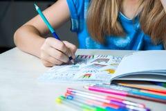 Kind die een kleurend boek schilderen Nieuwe spannings verlichtende tendens Stock Foto's