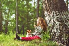 Kind die in een park onder een grote boom rusten