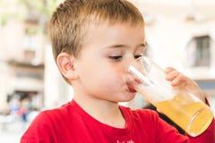 Kind die een soda in een glas drinken stock foto's