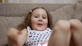 Kind die een spel op een mobiele telefoon spelen Het babymeisje downloadt de toepassing op smartphone stock video
