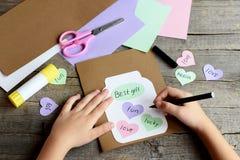 Kind die een verjaardagskaart doen Het kind houdt een zwarte teller in hand en schrijft Document groetkaart met kruik, harten en  Royalty-vrije Stock Foto's