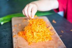 Kind die geraspte wortelen nemen Stock Afbeeldingen