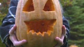 Kind die gesneden hefboom-o-lantaarn tonen aan camera, voorbereiding voor Halloween-vooravond stock videobeelden