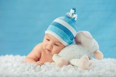 Kind die in hoed stuk speelgoed op een witte sprei koesteren Stock Foto