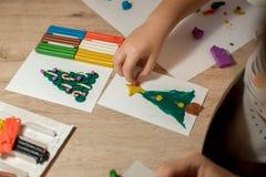 Kind die Kerstmisdecor van playdough maken bij lijst royalty-vrije stock afbeeldingen