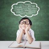 Kind die met boek toekomstige banen dromen stock fotografie