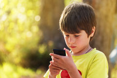 Kind die mobiele telefoon in openlucht spelen Stock Fotografie